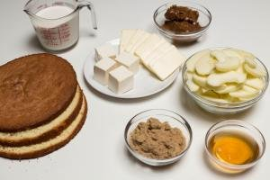 Ingredients on table including; cake slices, a bowl of brown sugar, a bowl of apple juice, a bowl of peeled and sliced apples, a bowl with dulce de leche, a plate with butter and cream cheese and a measuring cup with heavy whipping cream