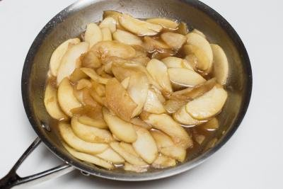 Apple juice and butter added to the pot with brown sugar and apples