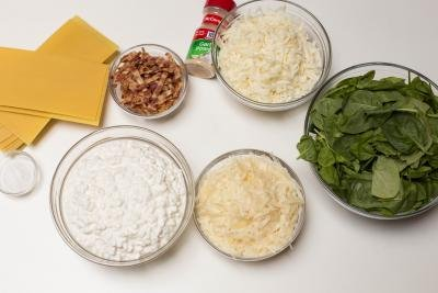 Ingredients on table including; a bowl with cottage cheese, a bowl with mozzarella, another bowl with parmesan, a bowl with spinach, a little bowl with bacon, garlic powder, a bowl with salt and dry lasagna pasta