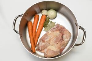 In a pot 3 carrots, an onion, garlic, bay leaves and frozen chicken drumsticks