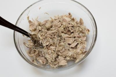Chicken in a bowl being pulled apart