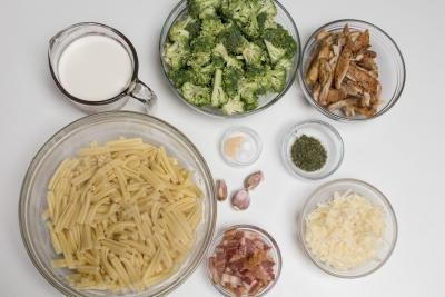 Ingredients on the table including; 5 bowls one with pasta, another with cheese, one with chicken, third with broccoli and fifth with bacon, a measuring cup with heavy whipping cream, and a little bowl with salt and garlic powder