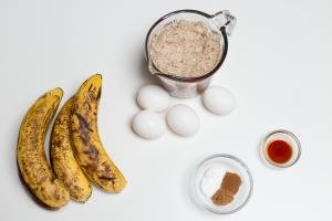 Ingredients on the table including; 3 bananas, 4 eggs, a measuring cup with almond meal flour, a little bowl with spices and a little bowl with vanilla extract