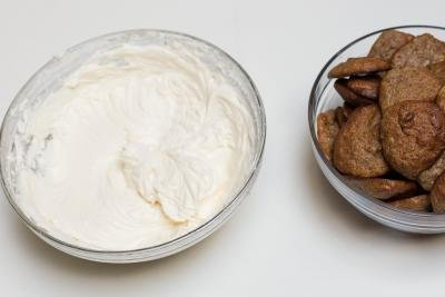 A bowl with Banana Almond Whoopie Pies and a bowl with cream cheese and powdered sugar mixture