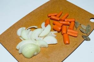 Carrots cut into large pieces, onions cut into half rings and bay leaves all on a cutting board