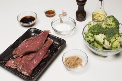 Ingredients on the table including; beef, a bowl of brown sugar, a bowl of broccoli, a bowl of corn starch, a bowl of soy sauce, garlic, salt and sesame oil