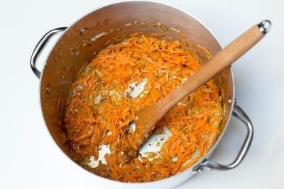 Onions and carrots being sautéed in a pot