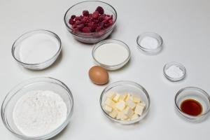 5 bowls one with flour, one with frozen berries, one with butter, another with sugar, and last bowl with milk, an egg, baking soda in a little bowl and vanilla extract in a bowl