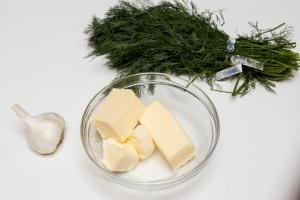 Butter in a bowl with garlic and dill next to it