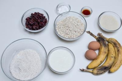 Ingredients on te table including; 7 bowls one with oats, another with dried cranberries, one with whole wheat flour, one with buttermilk, one with brown sugar, one with baking powder and last one with vanilla extract, also 3 bananas and 2 eggs