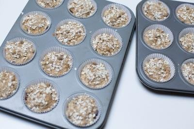 Cranberry Banana Oat Muffins in lined muffin tins with oats and sugar sprinkled on top of each muffin