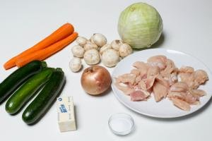 Ingredients on table including; cut up chicken on plate, a stick fo butter, an onion, 3 zucchinis, 2 peeled carrots, mushrooms, a cabbage and a little bowl with salt