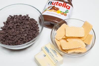 Ingredients on the table including; chocolate chips in a bowl, wafers in a bowl, 2 sticks of butter and jar of nutellla