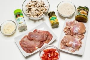 Ingredients on the table including; a plate with chicken thighs, a plate with prosciutto, a bowl with sliced tomatoes, a bowl with sliced mushrooms, a bowl with rice, a bowl with cheese, a jar of garlic salt, a jar of basil pesto, and a jar of better than bouillon chicken