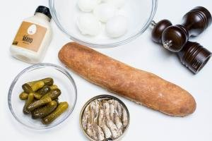 Ingredients on the table for egg & sprats canapes; sprats fish, baguette, pickles in a bowl, mayo, 5 eggs and salt and pepper