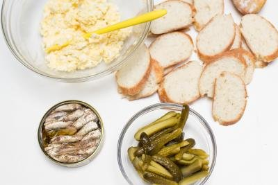 Table with sliced baguette and pickles, a bowl with egg and mayo mixture, and sprats