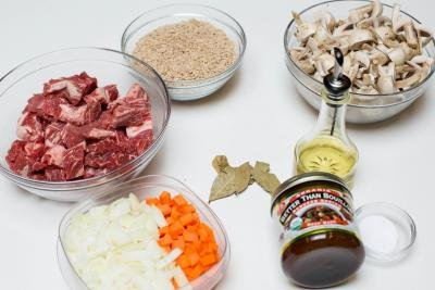 Ingredients on the table including; 4 bowls one with beef pieces, one with cut up onions and carrots, one with barely and one with cut up mushrooms, also a jar of better than bouillon beef, oil, bay leaves and a little jar of salt