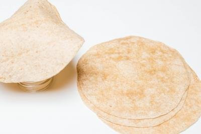 A pile of tortillas and one tortilla on top of the bottom of the jar