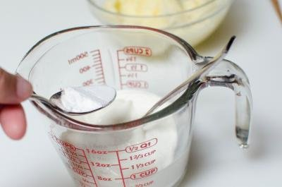In a measuring cup sour cream, baking powder and soda being mixed together with a spoon