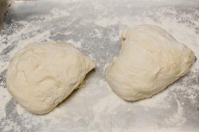 Dough formed into 2 oval balls on a floured surface