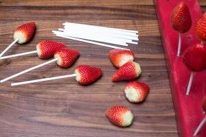 Lollipop sticks being placed into the top of the strawberries