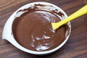 Melted chocolate in a bowl being stirred with a spatula