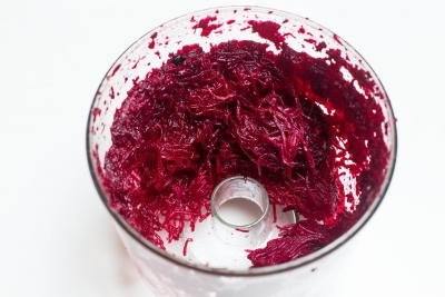 Beets in a food processor cut into thin slices