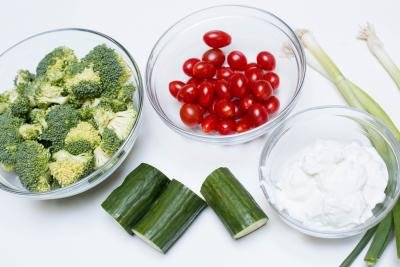 Ingredients on the table including; broccoli in a bowl, baby tomatoes in a bowl, grey yogurt in a bowl, cucumber and 3 springs of green onion