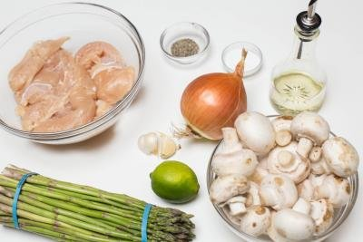A bowl with chicken, a bowl with mushrooms, asparagus, a lime, 3 cloves of garlic, an onion, oil, salt and pepper