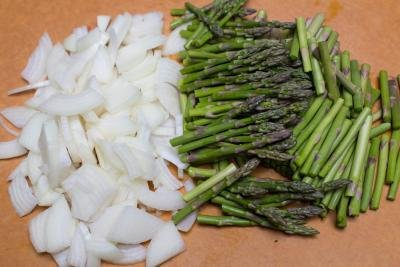 Diced onions and asparagus on a cutting board