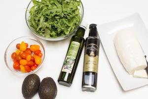 Ingredients on the table including; 2 avocados, a bowl of baby tomatoes, a bowl or arugula, olive oil, balsamic honey vinegar and mozzarella cheese