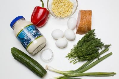 Ingredients on the table including; a cucumber, green onion, dill, 4 eggs, mayo, salt, a red bell pepper, corn in a bowl and bologna sausage