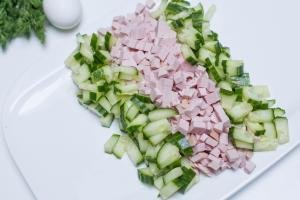 A rectangle plate with 2 rows of ingredients in order; sliced cucumbers, sliced bologna, and sliced cucumbers again