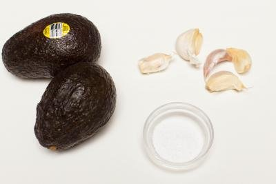 2 avocados, 5 garlic cloves and a little bowl of salt on the table