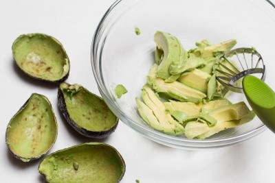 2 avocados being separated from the peel and placed into a bowl