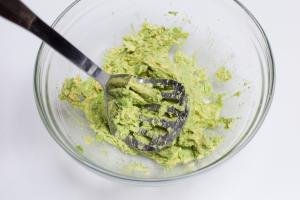 Avocado in a bowl being mashed with a potato masher