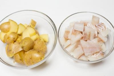 2 bowls one with cut up potatoes, one with cut up cod
