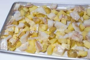 Cod and potatoes spread on a baking pan with butter spread on it