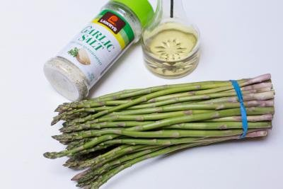 A bundle of asparagus, oil and garlic salt on the table