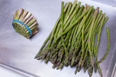 The bottom of the asparagus being cut off