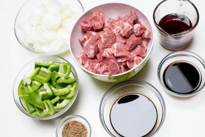 Ingredients for Lamb Kabobs on a table; bowl with green bell peppers, onions, lamb cut into one inch cubes, bowl with soy sauce, teriyaki sauce, red wine and steak seasoning