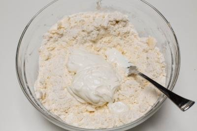 Sour cream being added into the bowl with the flour and butter