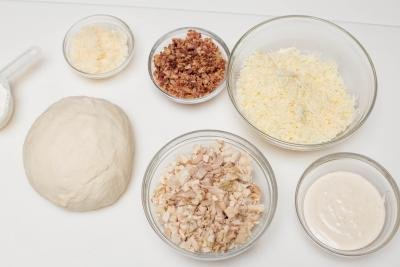 Ingredients in 5 bowls including; bacon, chicken, mozzarella cheese, parmesan, and ranch also dough besides the bowls