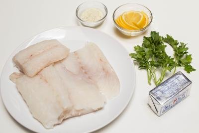 Cod on a plate, a stick of butter, a bowl with lemon slices, a bowl with garlic salt, and parsley on the table
