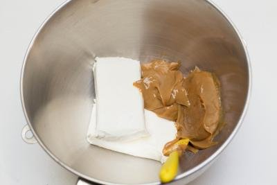 2 packets of cream cheese and dulce de leche placed into a mixing bowl with a spatula