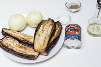 Ingredients on the table including; 2 halved eggplants on a plate, a jar of tomato sauce, 2 onions, a little bowl of salt and one with pepper