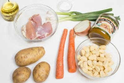 Ingredients on the table including; 3 potatoes, 2 carrots, dumplings in a bowl, a jar of 2better then bouillon chicken, half an onion, green onions, a bowl with chicken, a bowl with salt and oil