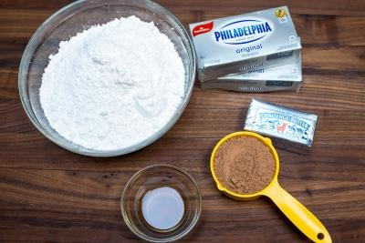 Ingredients on the table including; powdered sugar in a bowl, cocoa in a measuring cup, vanilla extract in a little bowl, butter and 2 packages of cream cheese