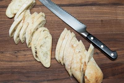 Baguette being sliced into thin slices on a cutting board