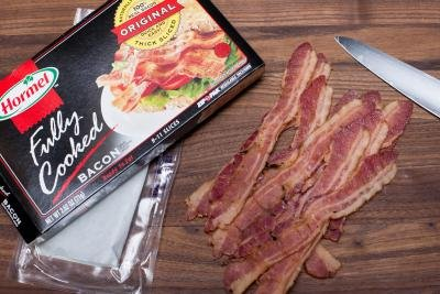 Fully cooked bacon removed from the package and placed onto the cutting board
